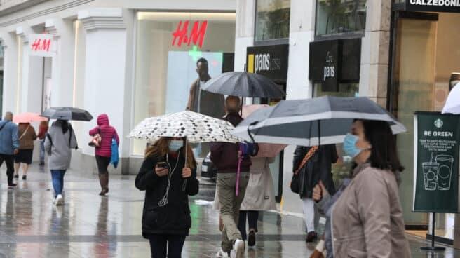 Transeúntes caminan por el centro de la capital protegiéndose de la lluvia con paraguas