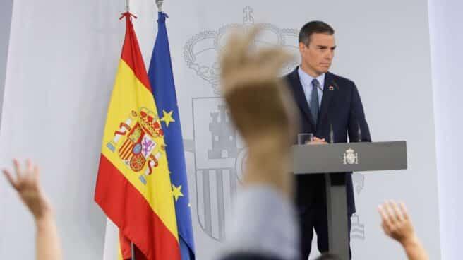 Periodistas levantan la mano para preguntar en una comparecencia de Pedro Sánchez en La Moncloa.