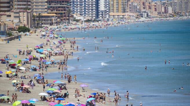 Varias personas se bañan en la Playa Galúa, en la Manga del Mar Menor.