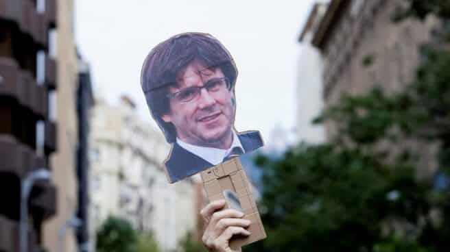 Una mano levanta una careta de Carles Puigdemont durante una manifestación en Barcelona.