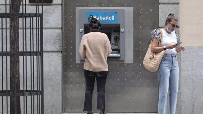 Dos mujeres frente a un cajero de Banco Sabadell.