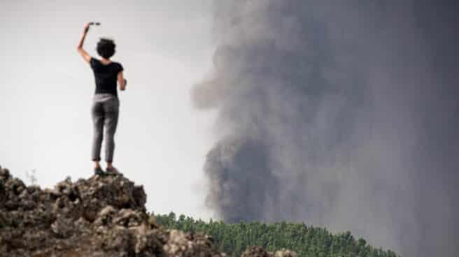 Una mujer fotografía el volcán con el móvil