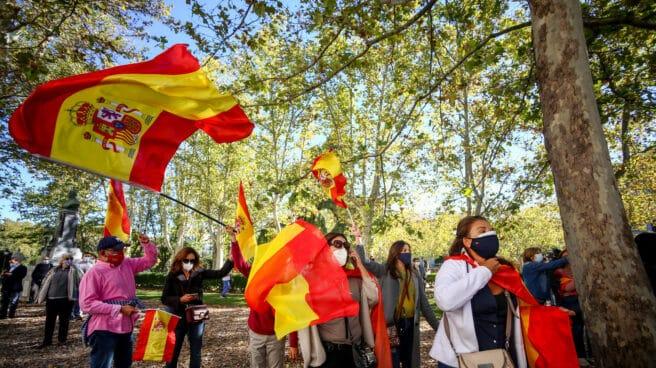 Varias personas se concentran con banderas de España en apoyo a la figura de Felipe VI