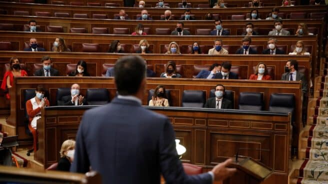 El presidente del Gobierno, Pedro Sánchez (de espaldas) contesta al líder del Partido Popular, Pablo Casado durante la sesión de control al Gobierno