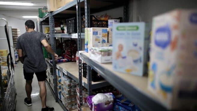 Un voluntario prepara productos antes de entregarlos a las puertas de la Parroquia Santa María Micaela de Madrid.