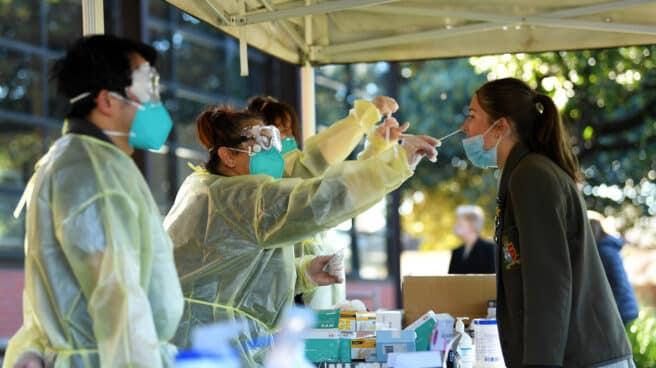 La estudiante de Firbank Grammar Year 11, Holly Fletcher (derecha), recibe una prueba de antígeno rápido COVID-19 administrada por un trabajador de TLC Healthcare en el campus de Brighton, Melbourne,