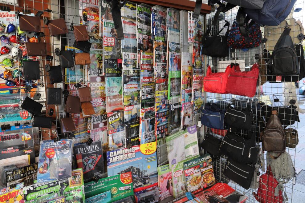 Productos como carteras y bandoleras se venden entre revistas y periódicos.