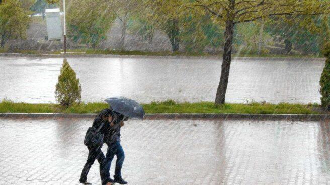 Día lluvioso en una calle. Dos personas bajo la lluvia con un paraguas