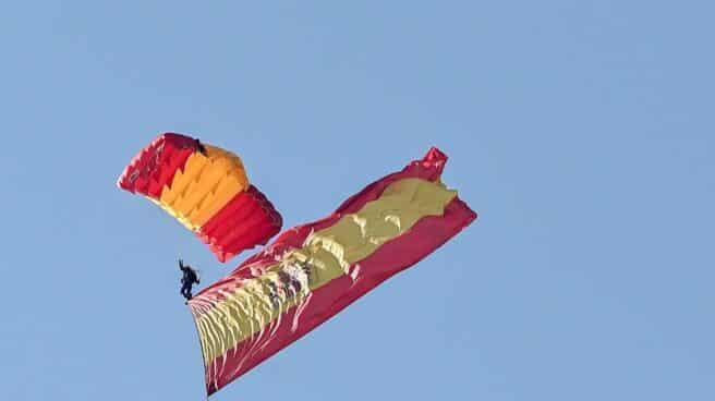 Un paracaidista del Ejército desciende sobre el Paseo de la Castellana en Madrid con la bandera de España.