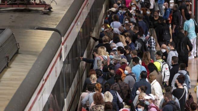 Pasajeros esperan acceder a un tren de Cercanías en la estación de Atocha en Madrid.