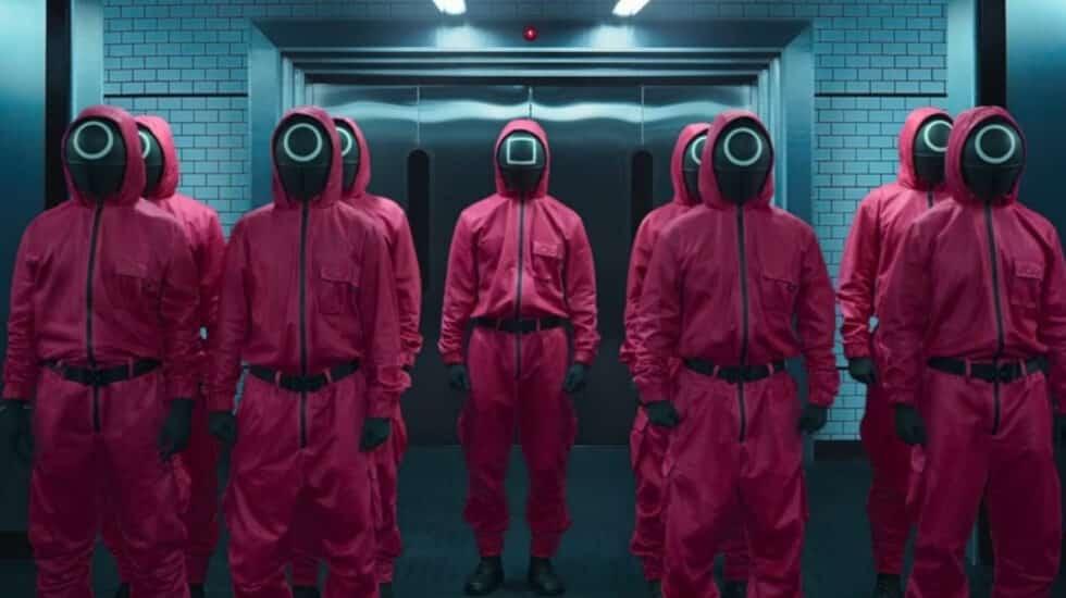 Escena de 'El Juego del calamar' donde aparecen 9 hombres vestidos con trajes rojos y la cara tapada por un símbolo