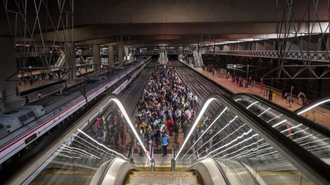 Un gran número de pasajeros espera la llegada de trenes en la estación de Madrid - Puerta de Atocha