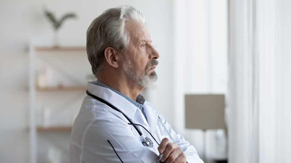 Imagen de un médico mirando a la ventana con cara de preocupación
