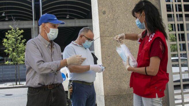 Miembro de la Cruz Roja entregando mascarillas