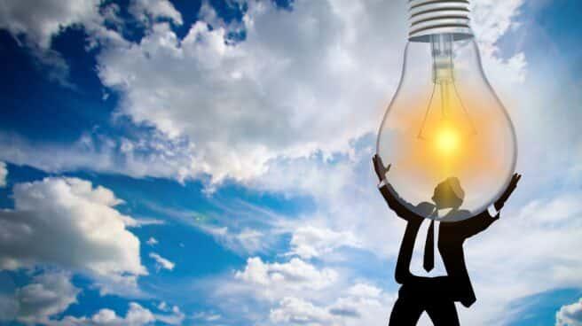Silueta de un hombre sujetando una bombilla encendida con el cielo de fondo