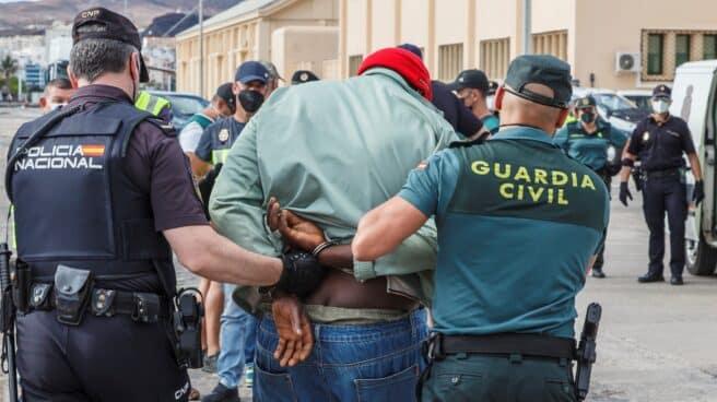 Un policía y un guardia civil conducen detenido a un hombre en una operación antidroga.