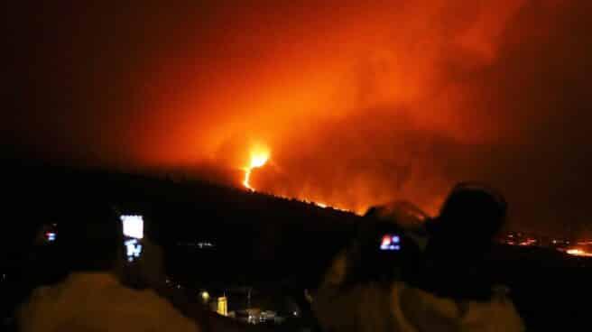Varias personas observan el avance de la lava desde el mirador de Tajuya.